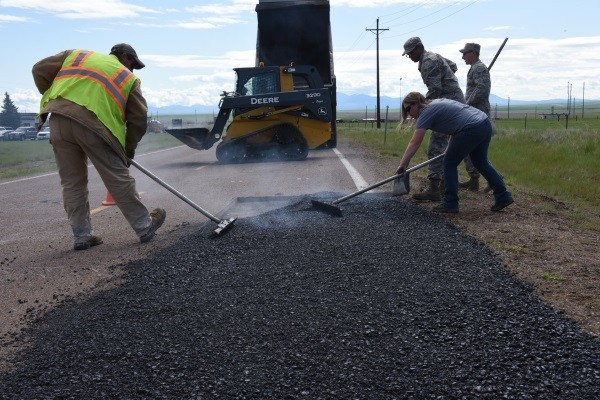 contractors shoving forward asphalt fragments to pave roads