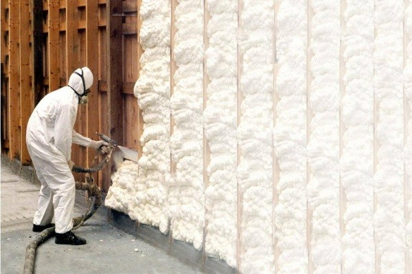 a spray urethane foam specialist applying the material to the walls