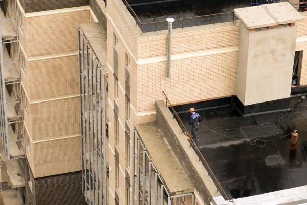 contractor inspecting black flat roof of building