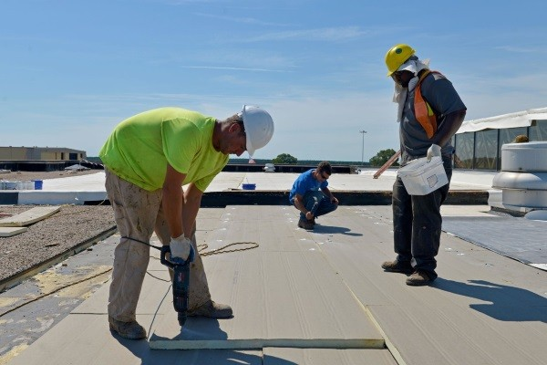 contractors working on a tar and gravel roof