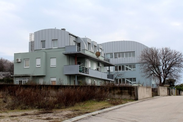 two apartments by the street with curved metal roof