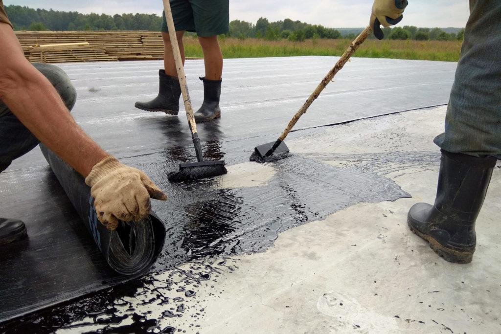 Roofer worker painting bitumen praimer e1603119395384